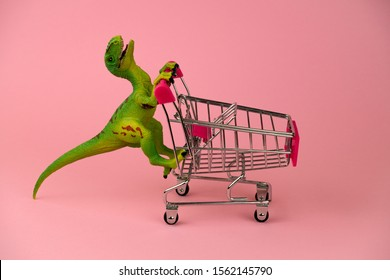 funny green dinosaur toy with shopping cart on a soft pink background