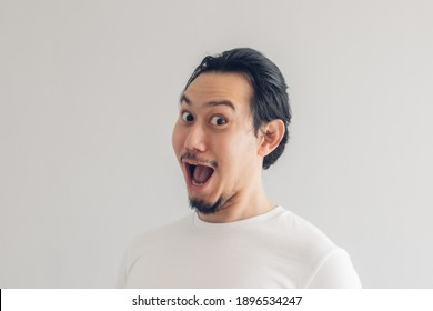 Funny grinning smile face of Asian man in white t-shirt and grey background.