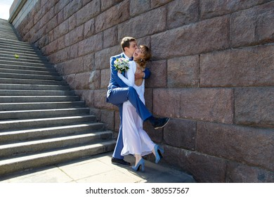 Funny groom and bride hugging near stairs in town