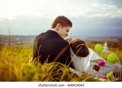 Funny groom looks at a bride while she lies on his knees on the field