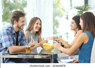 Funny group of 4 friends having a conversation and drinking at home