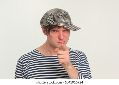 A funny guy in a cap and vest suspiciously pointing finger at you. Portrait.