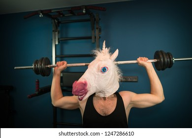 Funny guy in comical mask doing sport exercise. Unusual man pump up iron at home. Unicorn sportsman.