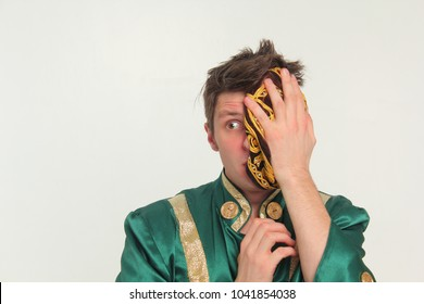 A funny guy in a green carnival costume, covered with a skullcap and suspiciously peeks. Portrait.
