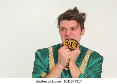 A funny guy in a green costume chews a skullcap and looks surprised. Portrait.