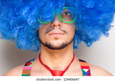 Funny guy naked with blue wig and red tie on white background
