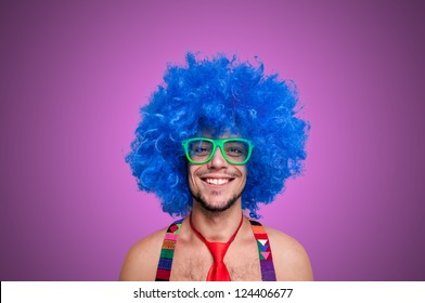 Funny guy naked with blue wig and red tie on pink background