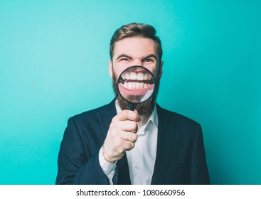 Funny guy is standing with the loupe and showing his teeth through it. Isolated on blue background