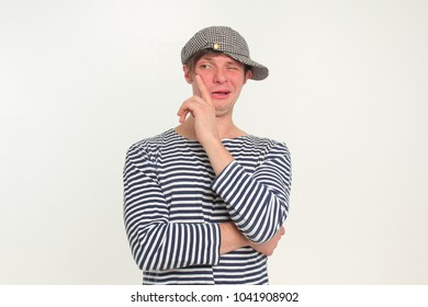 A funny guy in a vest and a cap with a funny emotion on his face. Portrait.