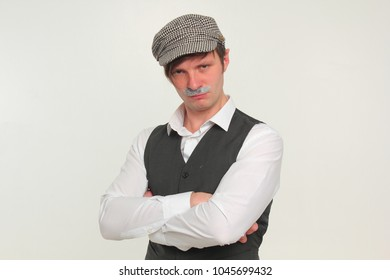 A funny guy in a vest and a cap with a fake mustache. Portrait.