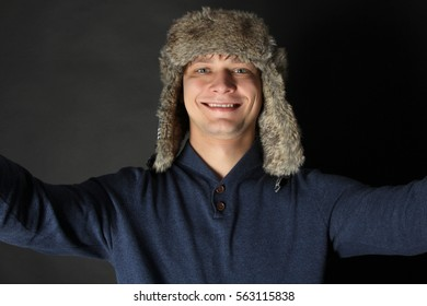 Funny guy in a warm hat makes selfie.