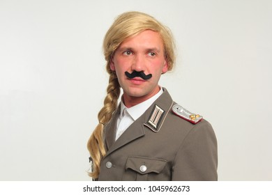 A funny guy in a wig, a fake mustache and a German uniform looks funny. Portrait.