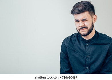 Funny handsome businessman looking at camera and winking.