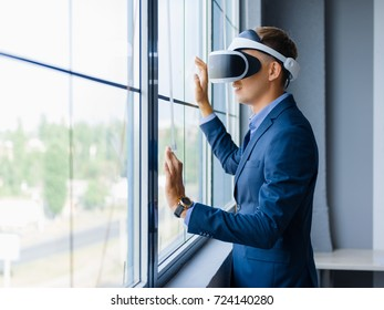 Funny handsome man wearing virtual reality glasses in modern interior design coworking studio. Smartphone using with VR goggles headset on blurred background. Business concept.