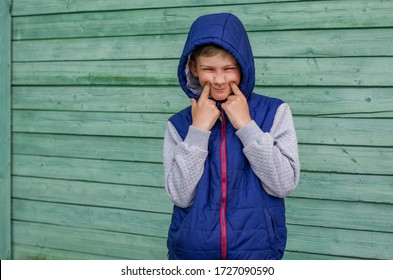 Funny handsome teenage boy is posing for camera. Outdoor portrait of a teenage boy on green background. Expressive boy with a hood on his head