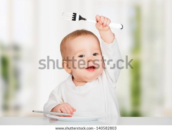 Drôle bébé heureux avec un couteau et une fourchette manger de la nourriture