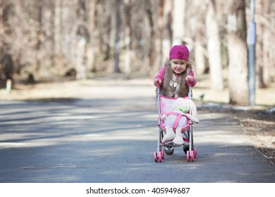 Funny happy beautiful pretty girl walking with toy pram in spring park