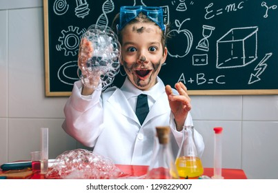 Funny happy boy dressed as chemist with dirty face after doing an experiment
