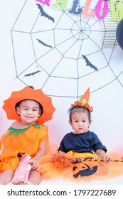 Funny happy brethren baby girl and kid boy in Halloween costume with pumpkin Jack with Cobweb on background, Halloween festival day concept