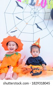 Funny happy brethren baby girl and kid boy in Halloween costume with pumpkin Jack with Cobweb on background
