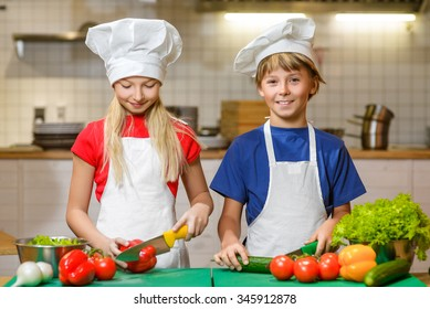 Funny happy chef boy and girl cooking at restaurant kitchen. concept of vegetarianism