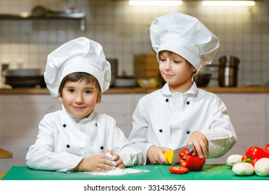 Funny happy chef boys cooking at restaurant kitchen