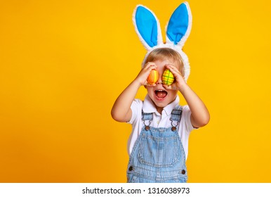 funny happy child boy with easter eggs and bunny ears on yellow background