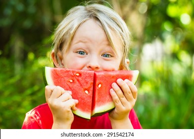 Funny happy child eating watermelon outdoors, making a smile