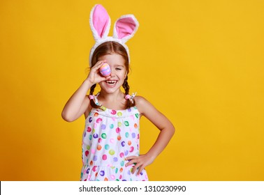 funny happy child girl with easter eggs and bunny ears on yellow background