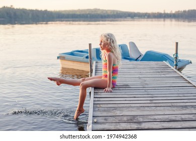 Funny happy cute Caucasian blonde girl child sitting on wooden dock pier by lake. Pensive kid in swimsuit splashing with legs in water. Summer fun outdoors activity. Happy childhood lifestyle.