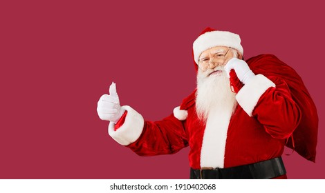 Funny happy excited old bearded Santa Claus face wearing costume looking at camera.