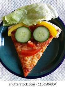 Funny happy face made from vegetables on a slice of pizza.