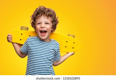 Funny happy kid in casual t-shirt holding longboard on shoulders looking super excited