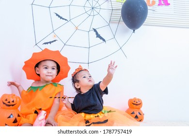 Funny happy little cute brethren baby girl and kid boy in Halloween costume with orange pumpkin Jack with Cobweb and black balloon in the home on white wall background, Happy Halloween day concept