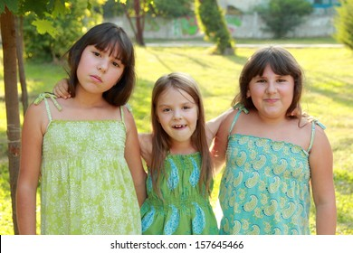 funny happy little girls fool around in the park