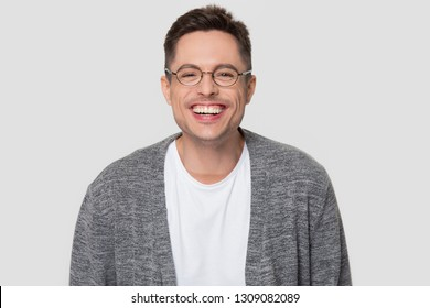 Funny happy millennial man wearing glasses laughing looking at camera, young guy chuckling smiling isolated on white grey studio blank background, male student nerd giggling having fun, portrait