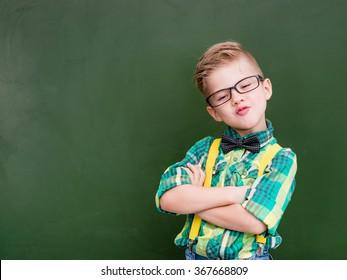 Funny happy nerd near empty green chalkboard