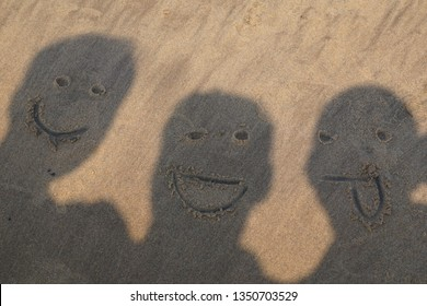 Funny and happy people shadow with smiley faces, friends funny faces shadow made at beach, Beach sand funny face shadows