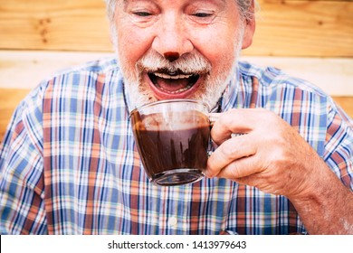 Funny happy senior people caucasian old man drinking hot chocolate and have it on nose and beard - laugh and have fun - concept of seniority and cheerful elderly retired lifestyle