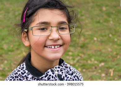 Funny happy smiling child girl wear too big glasses for fun