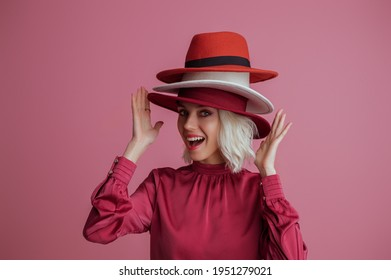 Funny, happy smiling fashionable  woman wearing many hats, posing on pink background. Model looking at camera. Fashion, sale, shopping advertising conception. Copy, empty space for text