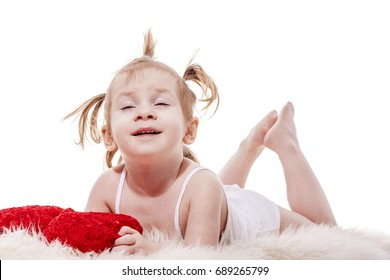 Funny happy toddler girl  lying in bed holding pillow isolated