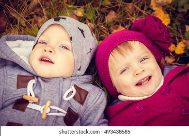 Funny happy twins boy and girl play in autumn leaves
