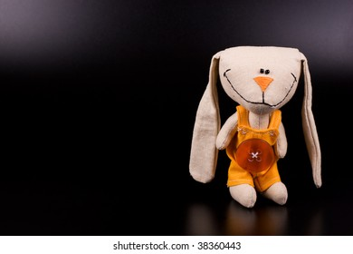 Funny hare toy on black background with copyspace