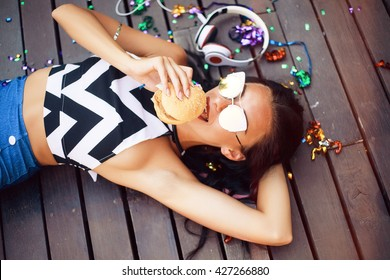 Funny Hipster Girl laying on wooden floor,hipster outfit Going Crazy at tropical island,Trendy Casual Fashion Outfit in summer,spring.Toned Photo,Copy Space.music on cool big headphones,burger,summer