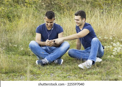 Funny hipster guys in trendy casual clothing reading e-book, listening music in park. White shiny smile. Bristle on face with healthy skin. Hipster style. Outdoor shot