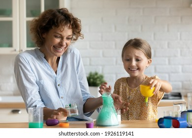 Funny home lab. Excited emotional parent mother daughter kid watch result of self made chemical test at home kitchen. Laughing young female babysitter help junior girl carry out scientific experiment