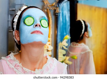 Funny housewife beauty green clay mask and cucumber at the mirror