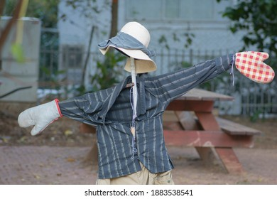 Funny Humanoid scarecrow, with a hat and oven mitts