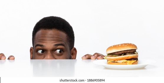 Funny Hungry African Guy Looking At Tasty Burger On Desk Having Food Craving Posing In Studio On White Background. Overeating Habit, Dieting And Nutrition, Cheat Meal Concept. Panorama